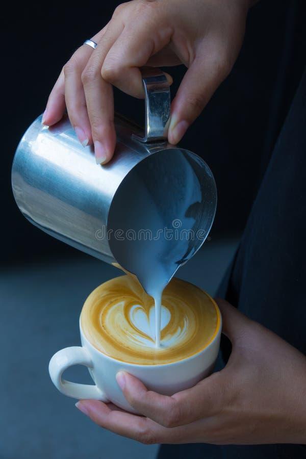 Cómo hacer el café del arte del latte de la hembra de Barista imagen de archivo libre de regalías
