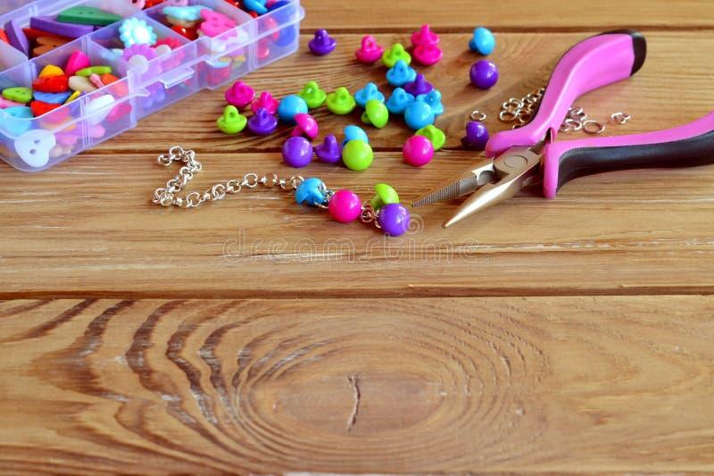 Cómo hacer la pulsera, artesanía de la diversión para los niños Manera hermosa de utilizar los botones Artes hechos con los boton foto de archivo