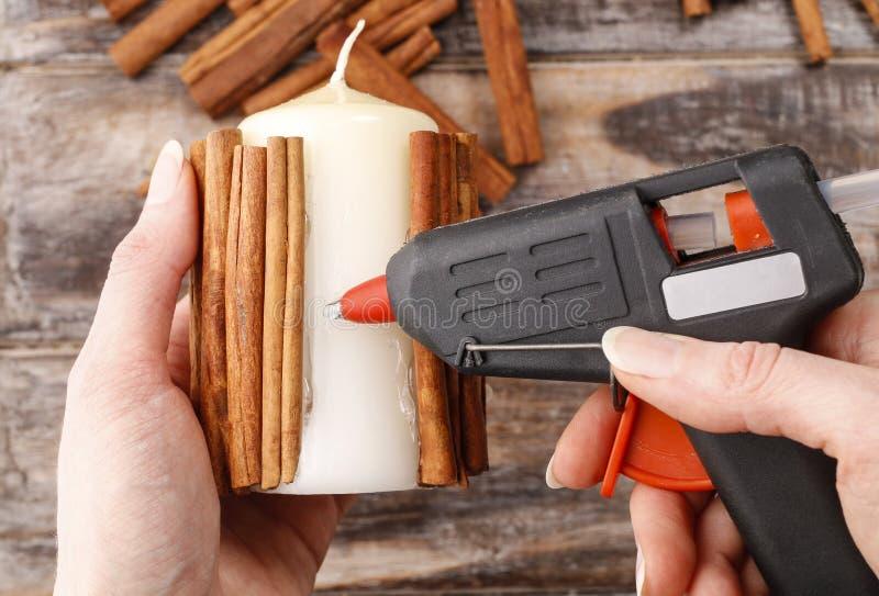 Cómo hacer la vela adornada con los palillos de canela preceptoral imagen de archivo libre de regalías