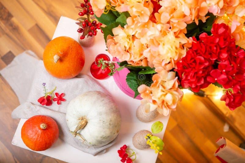 Cómo hacer una pieza central de la acción de gracias con la calabaza y el ramo grandes de flores fotografía de archivo libre de regalías