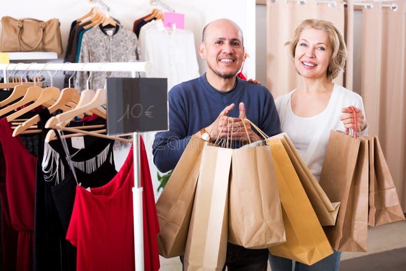 Cónyuges maduros que llevan bolsos con las compras foto de archivo libre de regalías