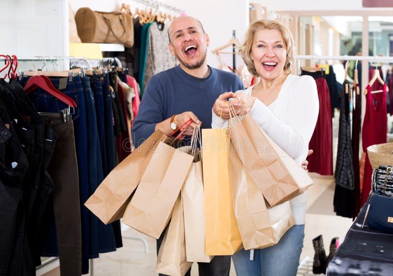 Cónyuges maduros que llevan bolsos con las compras fotos de archivo