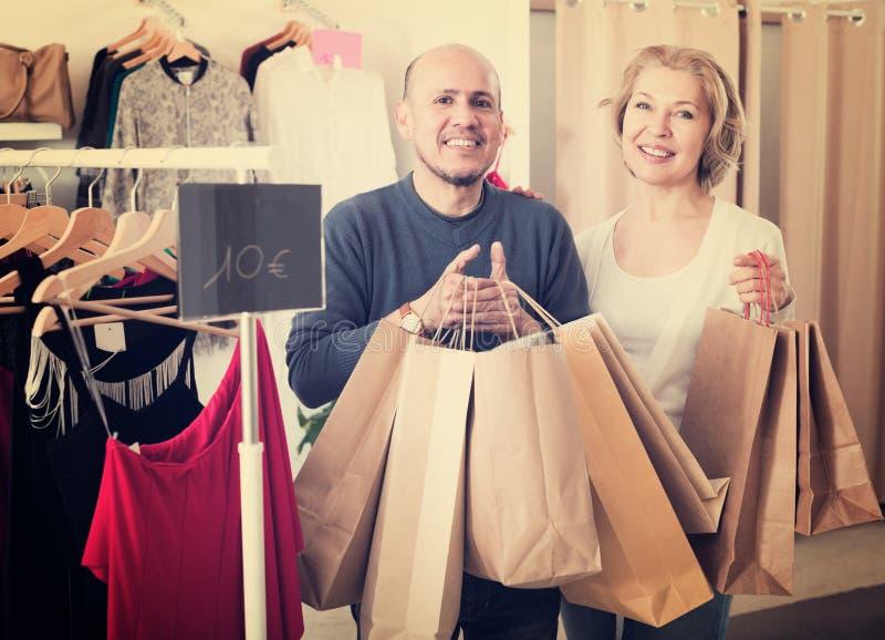 Cónyuges maduros que llevan bolsos con las compras imágenes de archivo libres de regalías