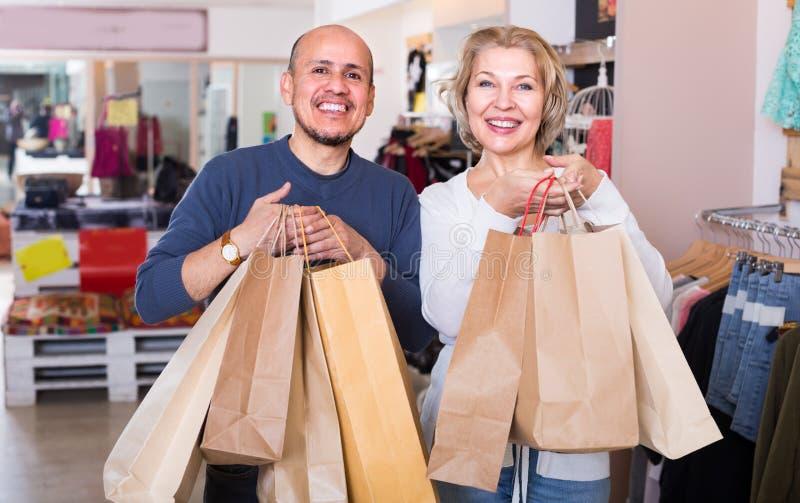 Cónyuges que llevan bolsos con las compras imagen de archivo libre de regalías