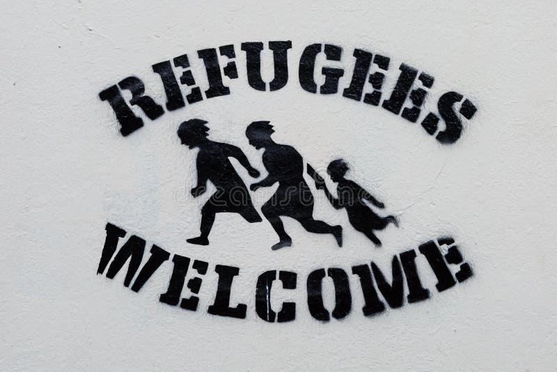 Cópia bem-vinda do estêncil do texto dos refugiados na parede branca imagem de stock royalty free