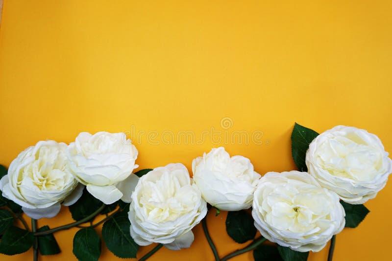 Cópia do espaço com o ramalhete artificial das flores da peônia no fundo amarelo fotos de stock