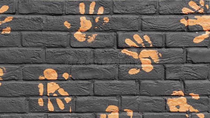 Cópias alaranjadas da mão na parede de tijolo preta Fundo fotos de stock royalty free