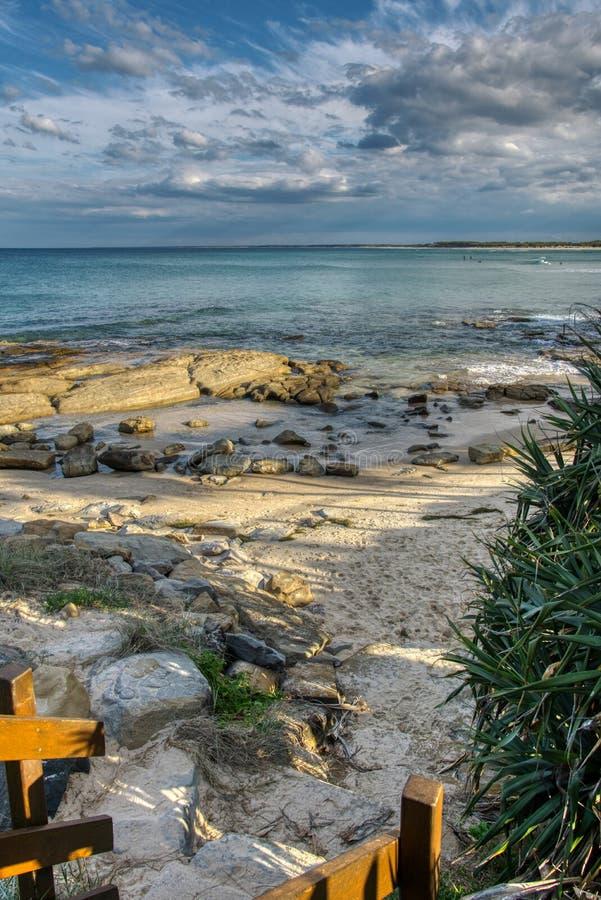 Cópias do pé da entrada da praia no céu azul das ondas macias da areia com nuvens, surfistas na distância imagens de stock royalty free