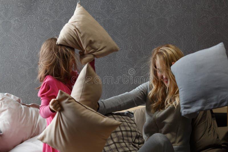Córka czyta książkę na łóżku podczas gdy mama śpi zdjęcie royalty free