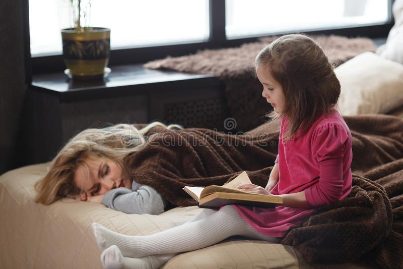 Córka czyta książkę na łóżku podczas gdy mama śpi obrazy stock