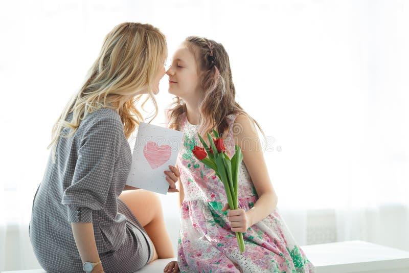 Córka dać jej matce bukietowi tulipany i pocztówce robić swój rękami zdjęcia stock