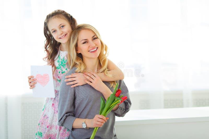 Córka dać jej matce bukietowi tulipany i pocztówka robić z jej swój wręcza zdjęcie royalty free