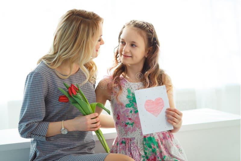 Córka dać jej matce bukietowi tulipany i pocztówka robić z jej swój wręcza macierzyństwo szczęśliwy zdjęcia royalty free
