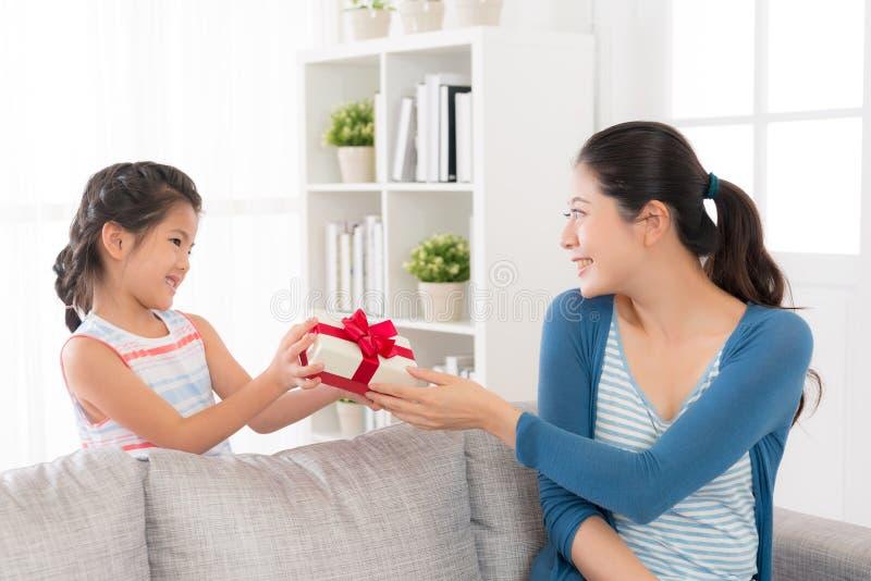 Córka daje jej matce czerwonemu tasiemkowemu prezenta pudełku obrazy stock