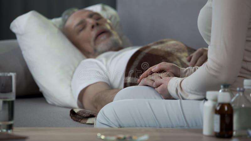 Córka dba o chorym ojca lying on the beach na kanapie, emerytura i chorobie, zdrowie zdjęcie stock