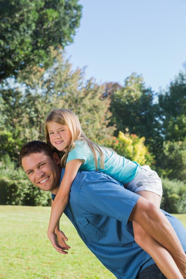 Córka dostaje piggyback od tata ono uśmiecha się przy kamerą zdjęcie royalty free