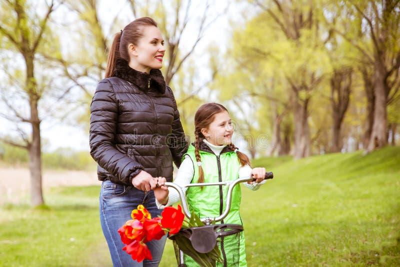 Córka i matka chodzimy wzdłuż brzeg jezioro z rowerem i opowiadamy Wartości rodzinne, edukacja obraz stock