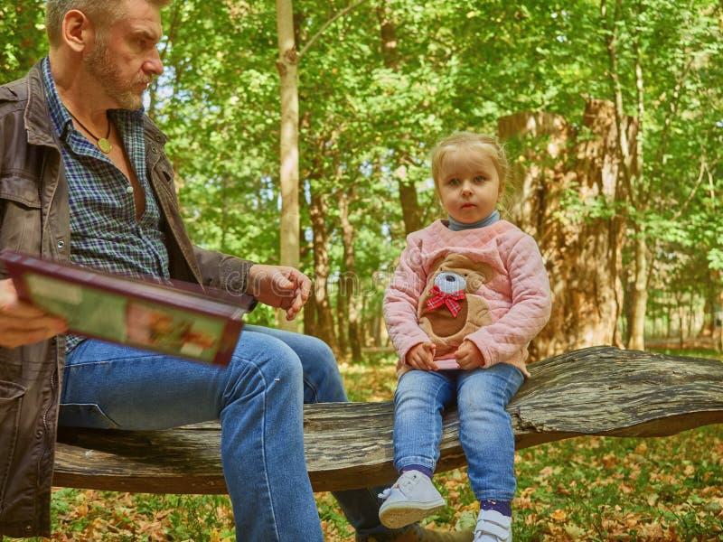 Córka, ojciec, potomstwa, książka, dom, dziecko, tata, piękny, obsiadanie, samiec, rodzinny wychowywać, śliczny, czytanie, trochę obraz royalty free
