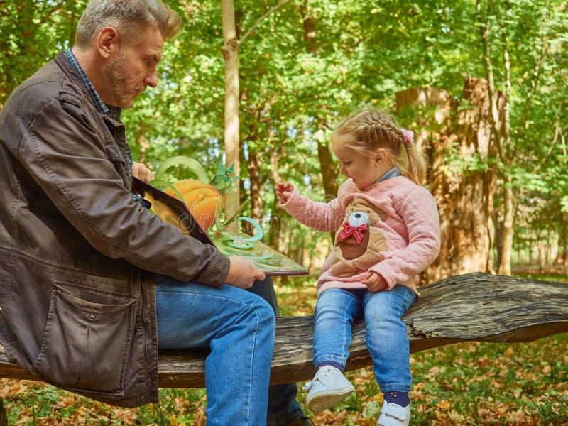 Córka, ojciec, potomstwa, książka, dom, dziecko, tata, piękny, obsiadanie, samiec, rodzinny wychowywać, śliczny, czytanie, trochę fotografia stock