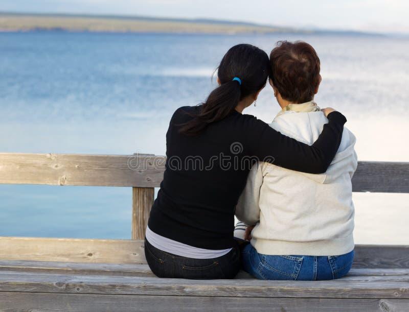 Córka pokazuje afekcję jej matka podczas gdy przy jeziorem fotografia royalty free