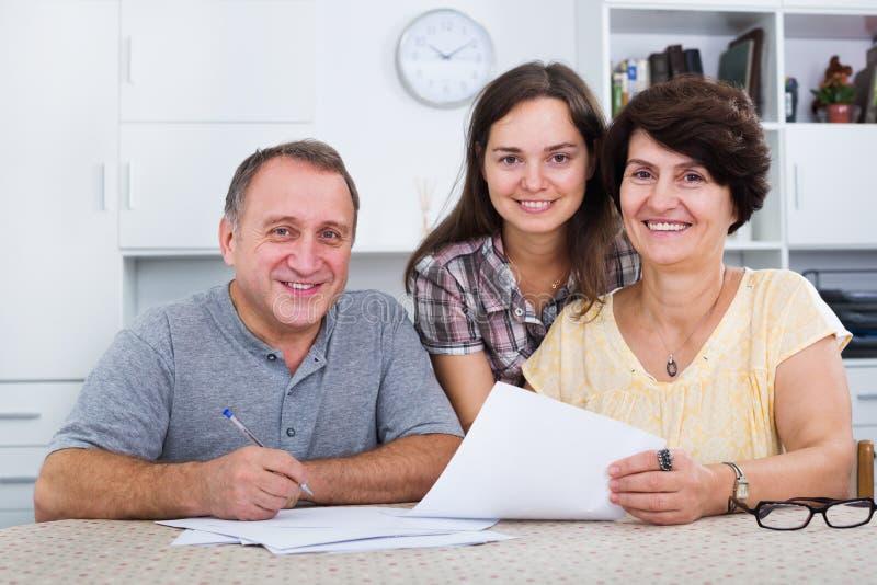 Córka pomaga z dokumentami rodzice fotografia stock