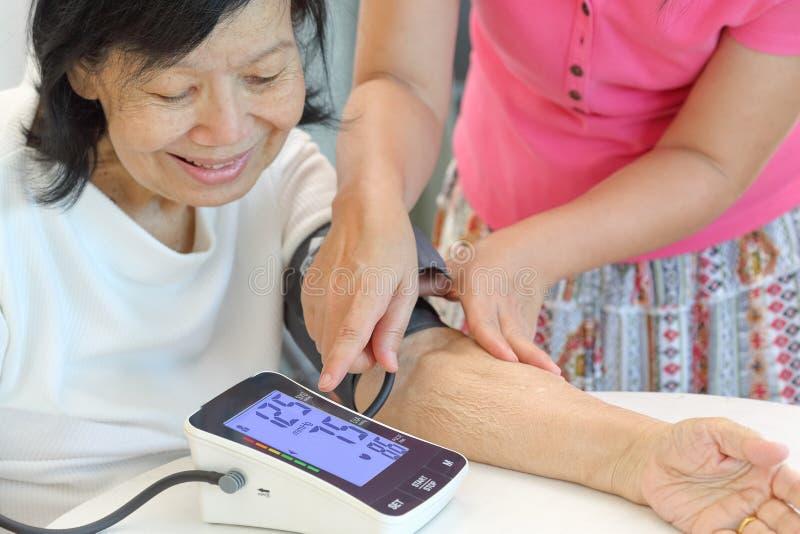Córka sprawdza macierzystego ` s ciśnienia krwi nadciśnienie zdjęcie royalty free
