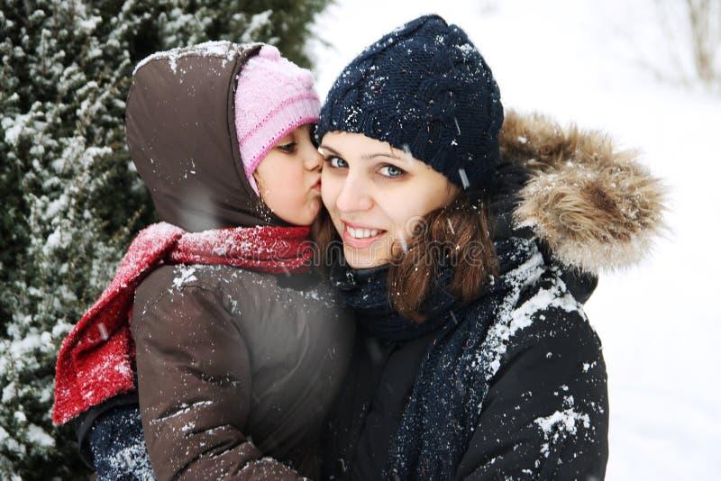 Córki całowania matka wśród śniegu obrazy stock