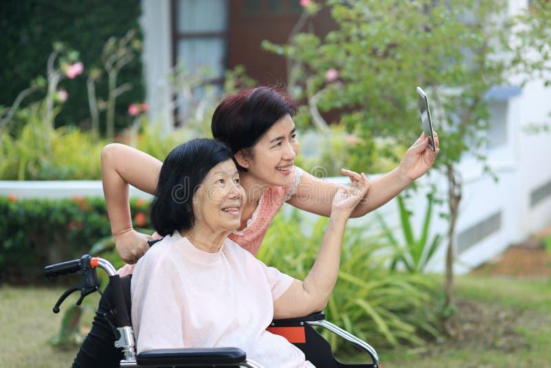 Córki czułość dla starszej azjatykciej kobiety, robi selfie zdjęcie stock