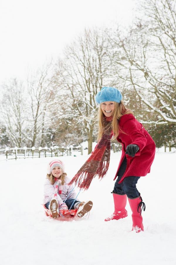 córki macierzysty ciągnięcia saneczki śnieg zdjęcie royalty free