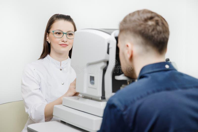 Córnea del control del doctor del oculista del ojo de la lámpara de la raja y oftalmólogo del examen de la retina foto de archivo libre de regalías