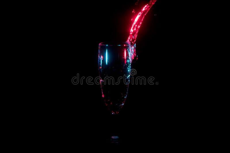 Córrego brilhante da água vermelha que derrama em um vidro isolado em um fundo preto imagens de stock