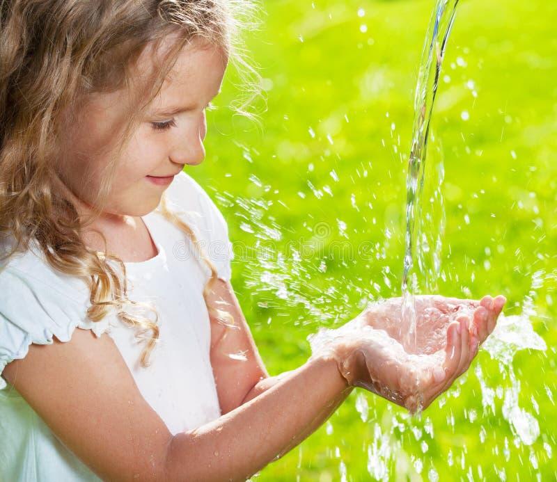 Córrego da agua potável que derrama em crianças as mãos foto de stock royalty free
