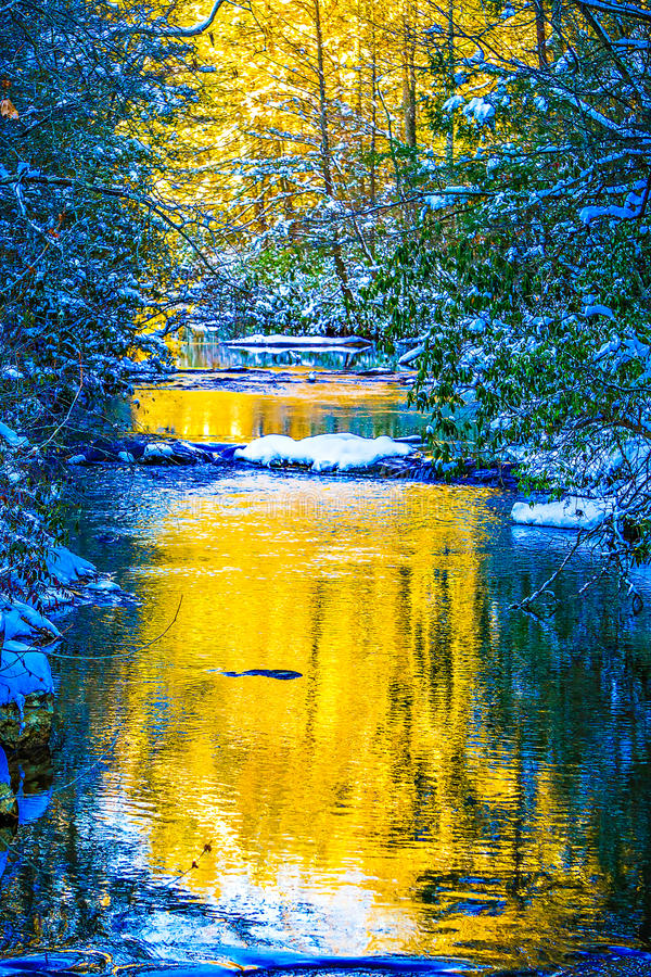 Córrego da montanha no por do sol com neve imagem de stock