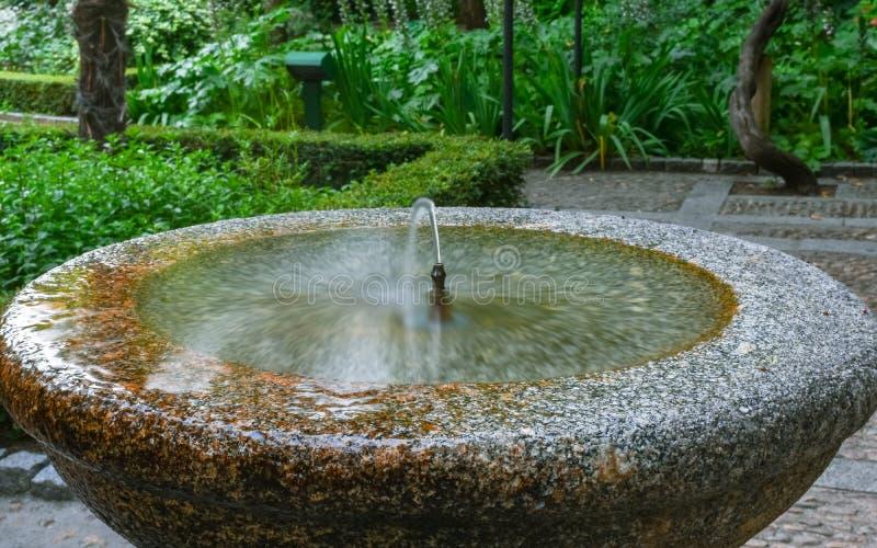 Córrego de jato da água potável de pedra da fonte foto de stock