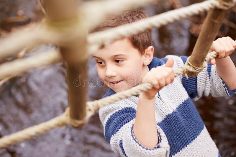 Córrego do cruzamento do menino na ponte de corda no centro da atividade fotografia de stock royalty free