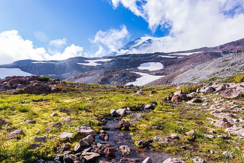 córrego do derretimento da neve que corre através de um landskape da montanha fotos de stock royalty free