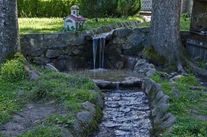 Córrego no pátio do St Cyril do monastério de Klisura e de St Methodius, fundado no século XII com uma cachoeira fotografia de stock