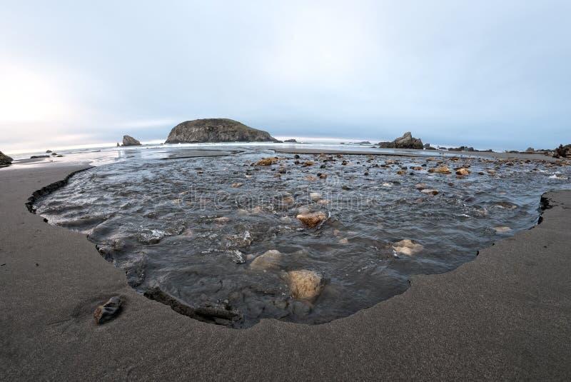 Córrego que cinzela afastado a praia imagem de stock royalty free