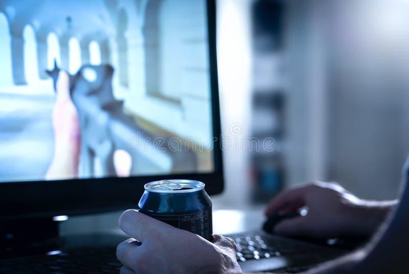 Córrego vivo de fluência ou de observação do indivíduo do jogo de vídeo em linha ao beber a bebida ou a soda da energia da lata fotos de stock