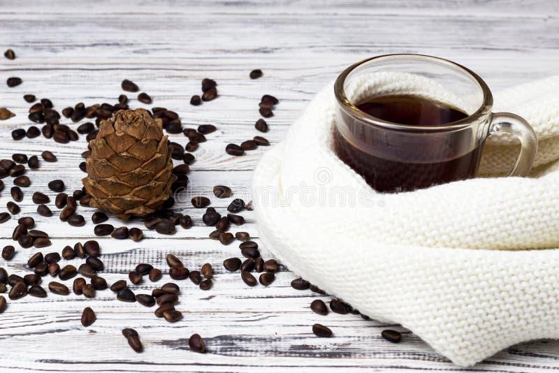 Cône de cèdre et pignons, une tasse de thé sur un fond en bois blanc, plan rapproché, écharpe photos stock