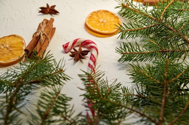 Cône rouge de sucrerie avec la fin d'étoile d'anis sur le fond blanc décoré des bâtons de cannelle, des oranges sèches et de la b photo libre de droits