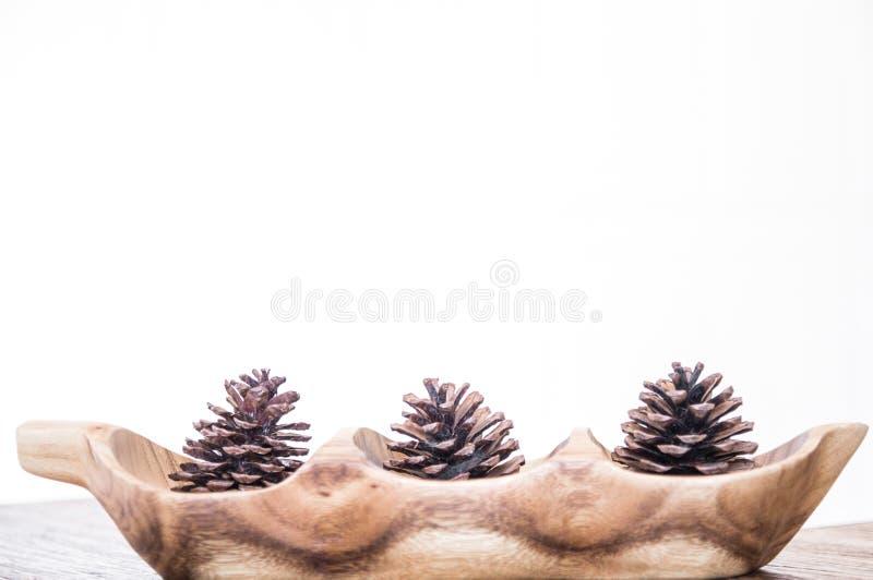 Cônes d'un pin sur le plat en bois dans les coups sur le fond blanc image libre de droits