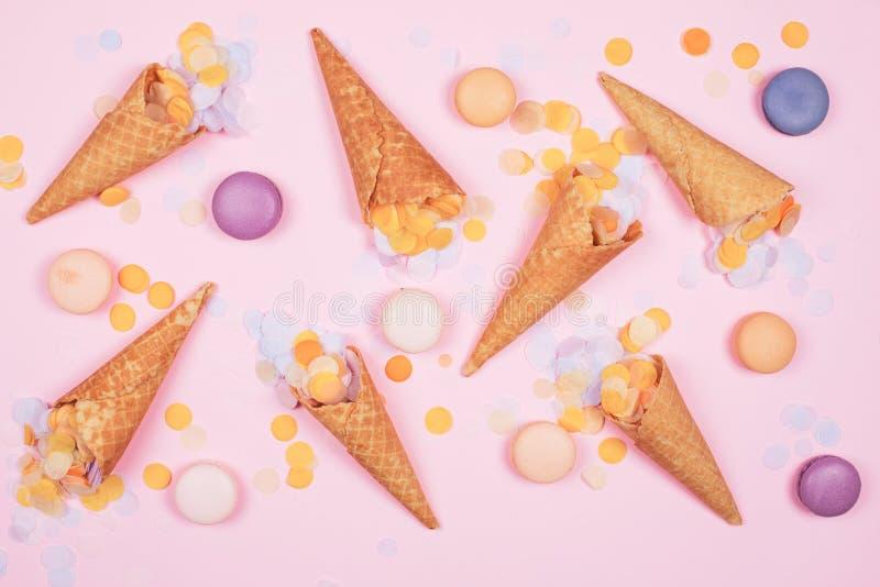 Cônes de gaufre de crème glacée avec des macarons et confettis sur le fond rose images libres de droits