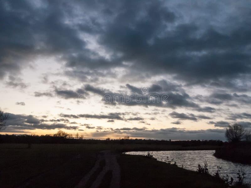 Côté réglé de campagne de ciel nocturne du soleil dramatique de rivière photo stock