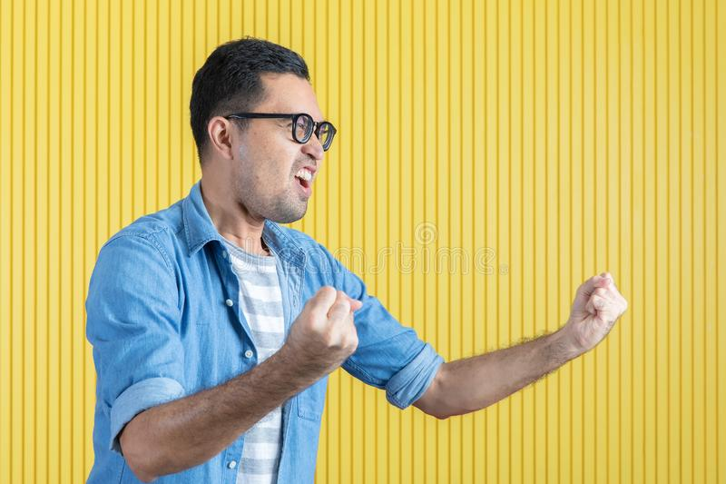 Côté-vue, fin du jeune homme barbu bel asiatique, lunettes de port, dans la chemise de denim, indiquant par espièglerie son côté  photo stock
