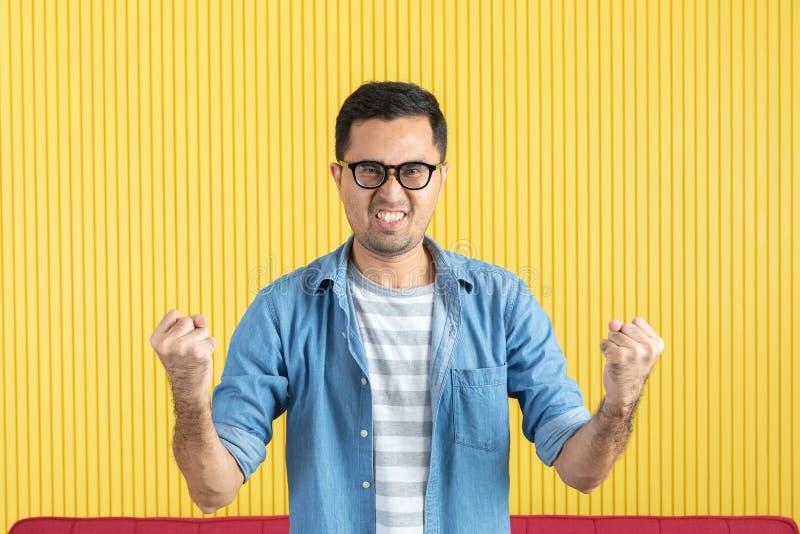 Côté-vue, fin du jeune homme barbu bel asiatique, lunettes de port, dans la chemise de denim, indiquant par espièglerie son côté  images libres de droits