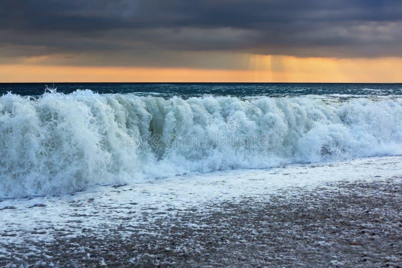 Côte avec des ondes ; le soleil est apparu par des nuages photo libre de droits