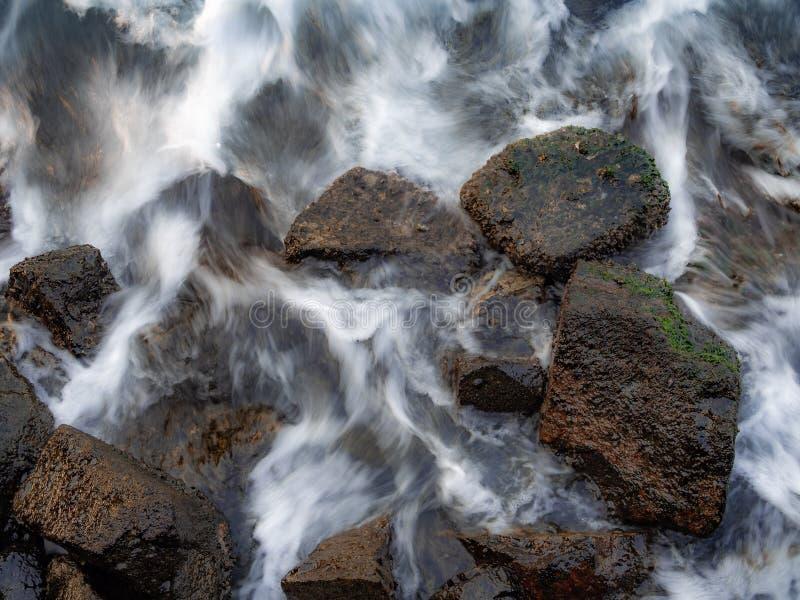 côte liée par roche avec de l'eau soyeux ondulant de nouveau à la mer photos libres de droits