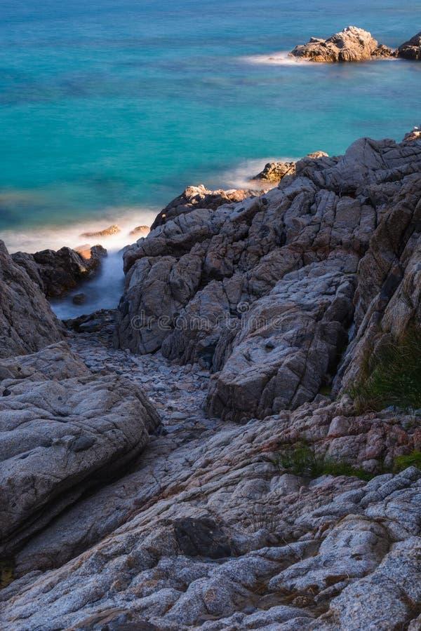 Côte rocheuse avec le feuillage vers les eaux vertes photo stock