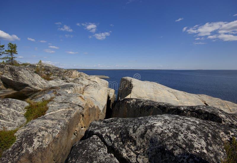 Côte rocheuse de l'île granitique à la lumière du soleil image stock